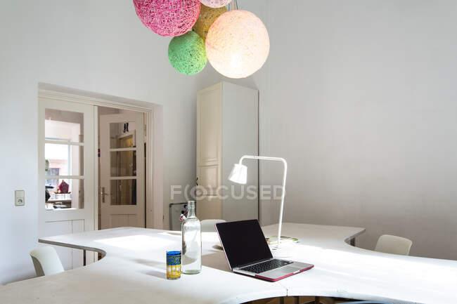 Ordenador portátil en la mesa en la oficina en casa moderna - foto de stock
