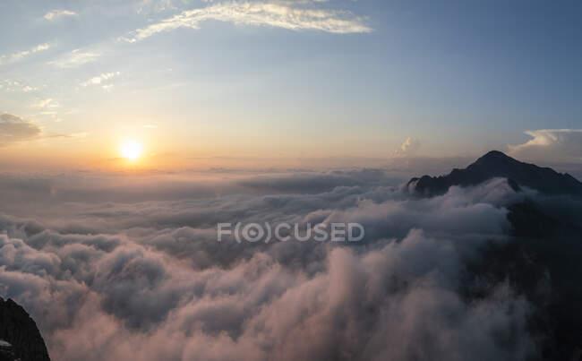 Idilliaco colpo di montagna coperto di nuvole durante l'alba alle Alpi Bergamasche, Italia — Foto stock