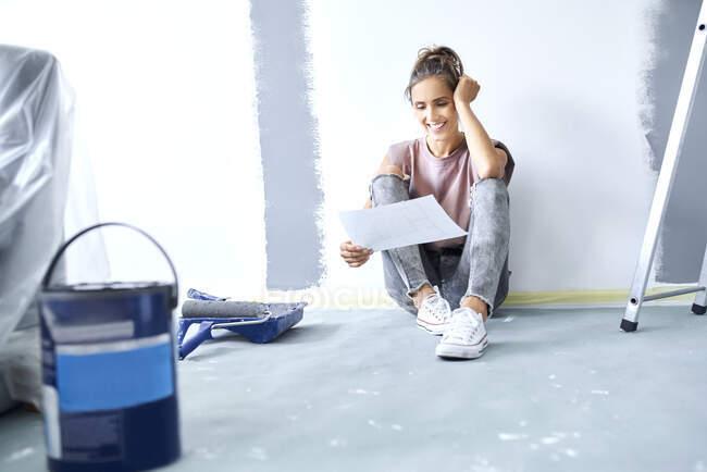 Посмішка жінка з головою в руках тримає папір, сидячи на підлозі вдома. — стокове фото
