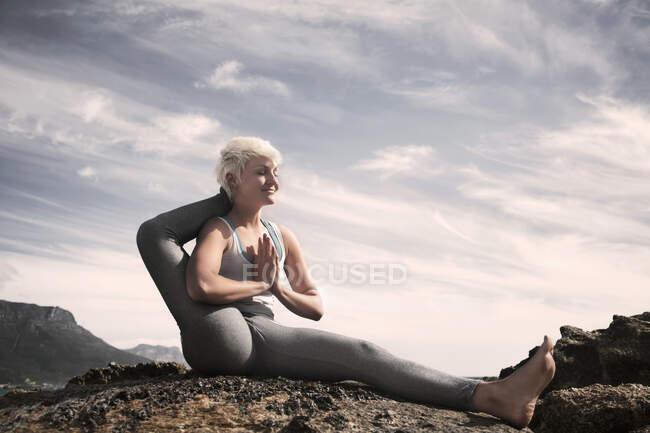 Улыбающаяся гибкая женщина с закрытыми глазами практикующая эка пада сирсасасана на пляже против неба — стоковое фото