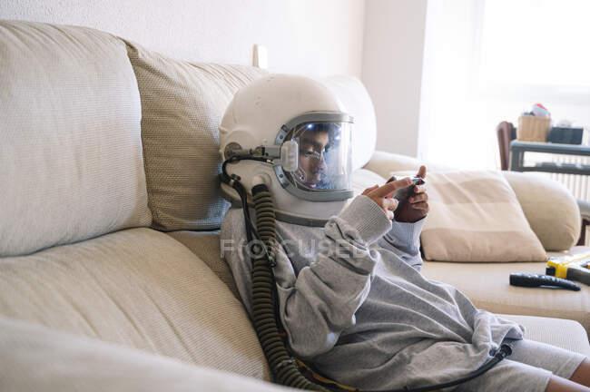 Ragazzo che indossa il casco spaziale giocare a videogiochi palmari mentre si rilassa sul divano a casa — Foto stock