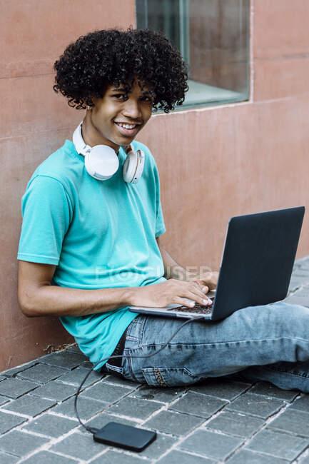 Jovem sorridente usando laptop enquanto se senta no caminho da cidade — Fotografia de Stock