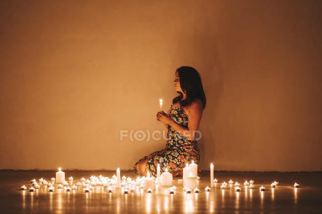 Mujer con velas iluminadas en salón en casa - foto de stock