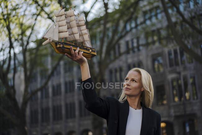 Empresa rubia confiada mirando el modelo de velero mientras está de pie en la ciudad - foto de stock