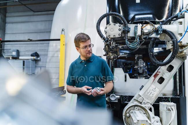 Trabalhador manual masculino olhando para braço robótico enquanto segurando parte da máquina na indústria — Fotografia de Stock