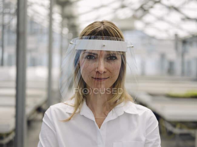 Primer plano de empresaria confiada que usa protector facial en invernadero - foto de stock