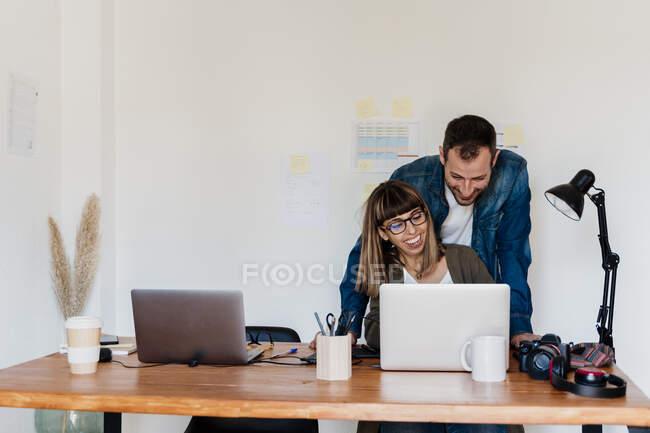 Усміхнена ділова пара працює разом на ноутбуці в домашньому офісі. — стокове фото