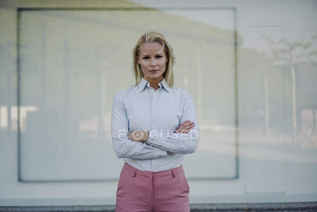 Confident beautiful blond female entrepreneur standing with arms crossed against wall — Stock Photo