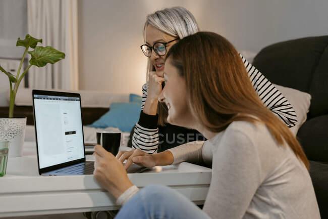 Жінки роблять онлайн-покупки на ноутбуці, сидячи вдома. — стокове фото