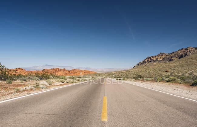 Зсушуючий вид на порожню пустельну дорогу проти блакитного неба (штат Невада, США). — стокове фото