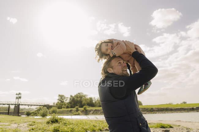 Батько бавиться з донькою, коли забирає її у сонячний день. — стокове фото