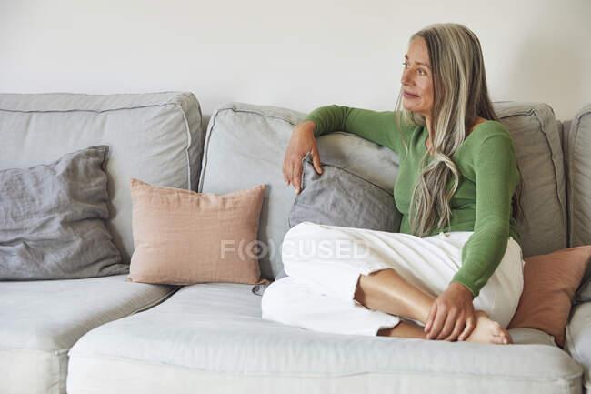 Зрелая женщина мечтает, сидя дома на диване — стоковое фото