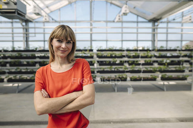 Smiling female entrepreneur with arms crossed standing against plants at nursery — Stock Photo