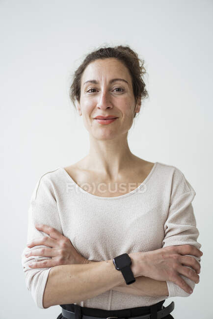 Close-up of smiling female entrepreneur with arms crossed standing against wall — Stock Photo