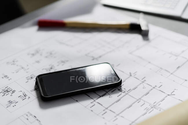 Smart phone and hammer lying on architectural blueprint — Stock Photo