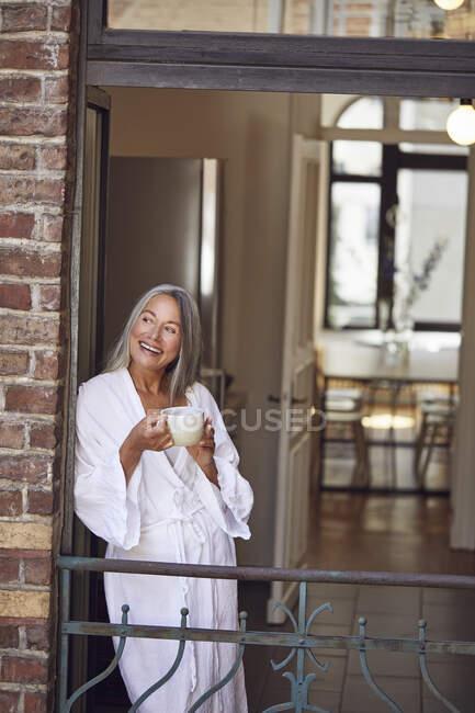 Happy woman drinking tea in balcony — Stock Photo