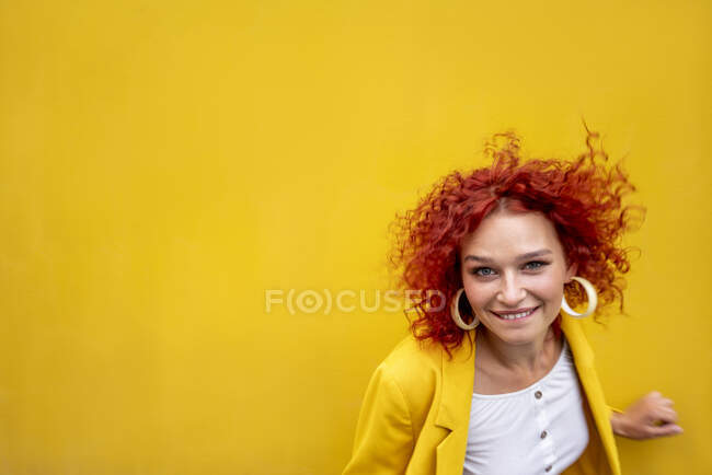 Happy young woman with red curly hair in front of yellow wall — Photo de stock