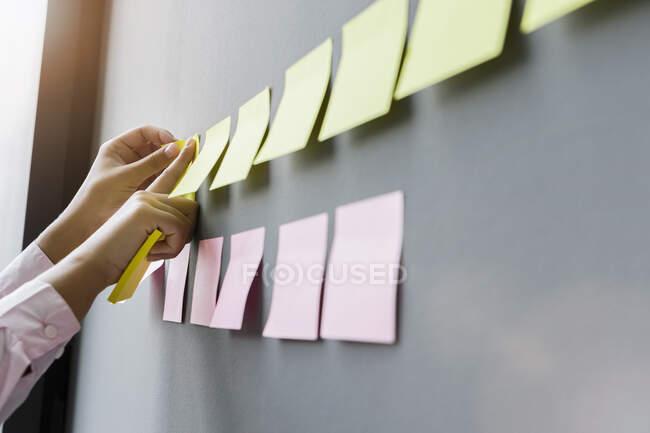 Руки ділової жінки наклеюють клейкі нотатки на стіні в офісі — стокове фото