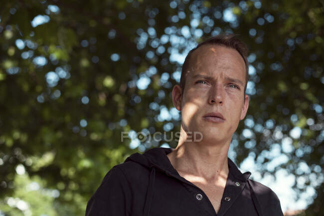 Thoughtful man looking away against trees in park — Stock Photo