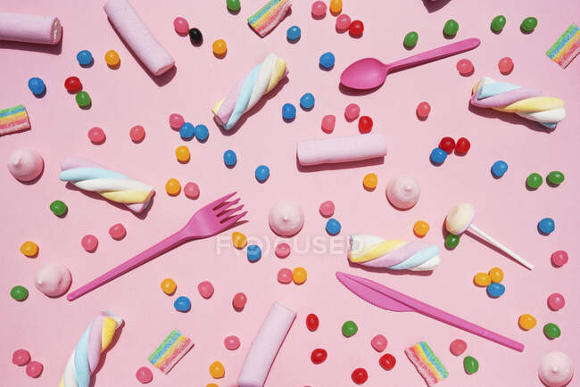 Varios dulces sobre fondo rosa - foto de stock