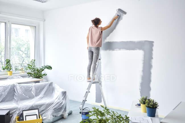 Молода жінка малює стіну з больовим роликом, стоячи на драбині вдома. — стокове фото