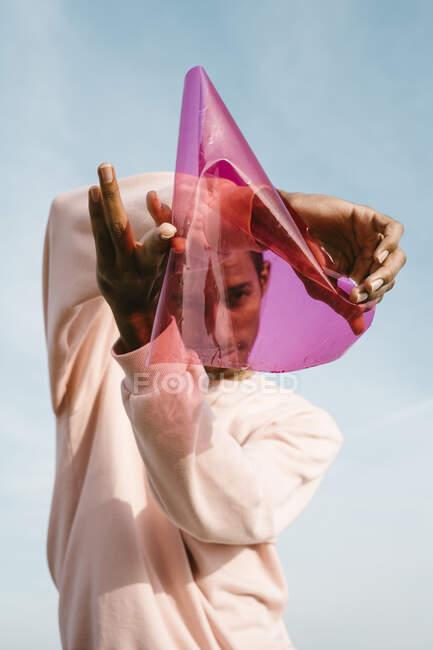 Hombre jugando con plástico rosa mientras está de pie contra el cielo - foto de stock