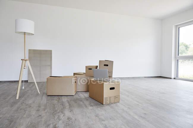 Interior de la habitación moderna con cajas de cartón, lámpara eléctrica y ordenador portátil - foto de stock