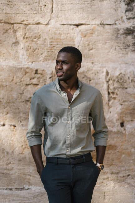 Молодой бизнесмен с руками в карманах стоит у стены — стоковое фото