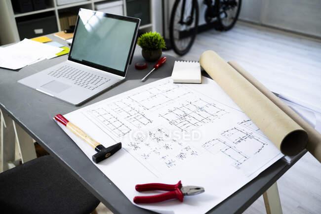 Ordenador portátil y plano arquitectónico acostado en el escritorio en el estudio - foto de stock