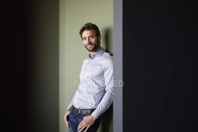 Businessman smiling while standing against green wall in office — Stock Photo