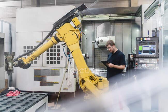 Trabalhador da fábrica masculino usando tablet digital em pé na frente de braços robóticos na indústria — Fotografia de Stock