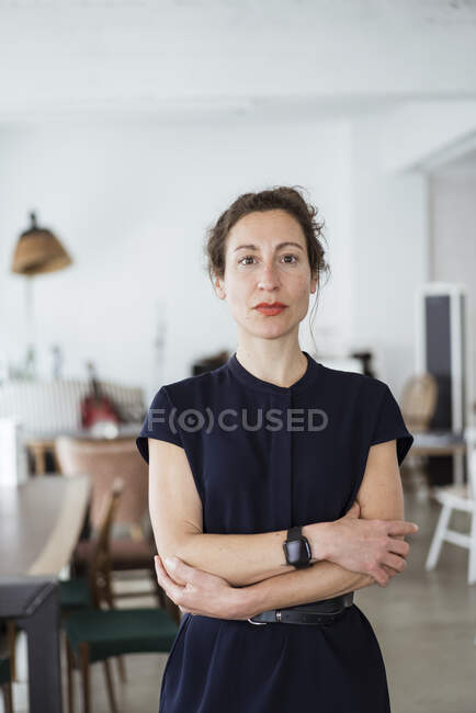 Confident female owner with arms crossed standing in restaurant — Stock Photo