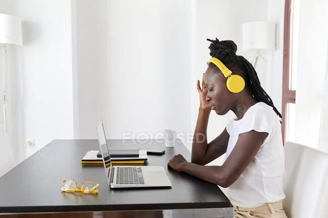 Mujer joven con auriculares con los ojos cerrados sentado en el escritorio en la oficina en casa - foto de stock