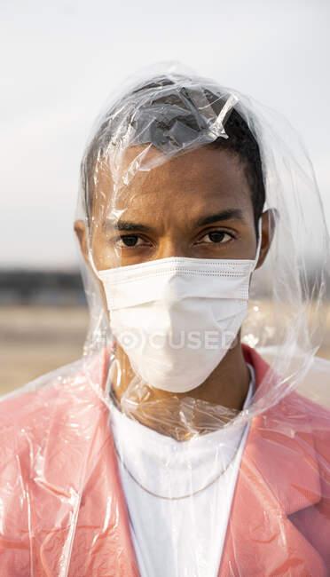 Hombre con impermeable y mascarilla protectora mirando mientras está parado al aire libre - foto de stock