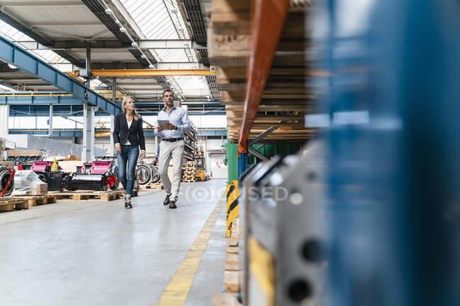 Бизнесмен и коллеги-женщины с цифровым планшетом при ходьбе в промышленности — стоковое фото