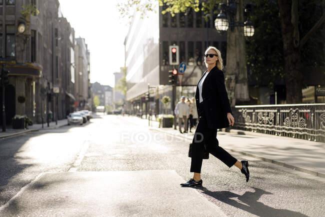 Дивна жінка, яка перетинає вулицю в місті. — стокове фото