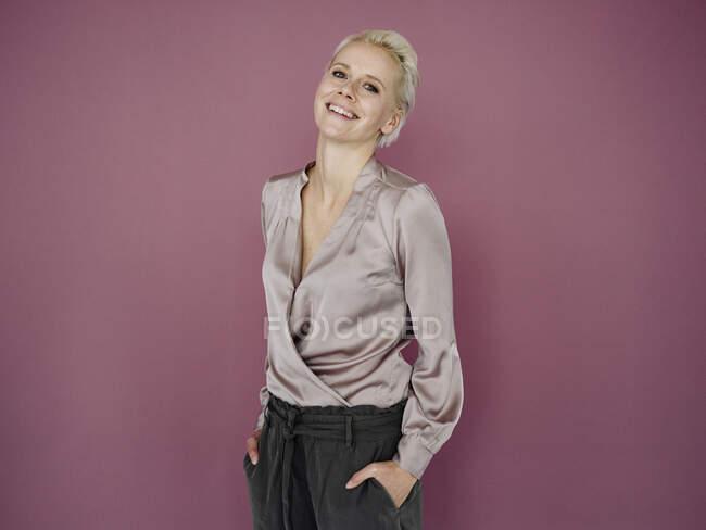Посміхаючись, жінка - підприємець тримає руки в кишенях, стоячи навпроти пурпурового фону. — стокове фото