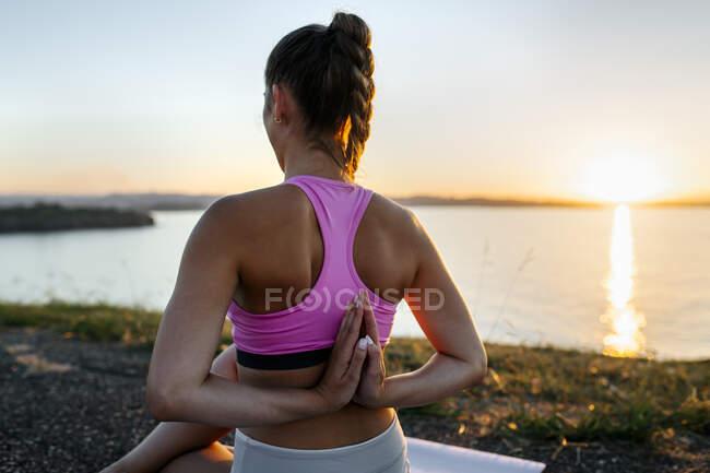 Молодая женщина, практикующая молитву, позирует у моря на закате — стоковое фото