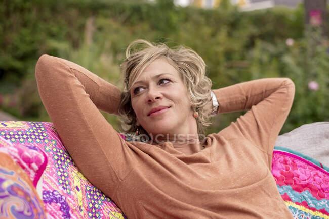 Mujer sonriente sentada con las manos detrás de la cabeza en el sofá en el patio trasero - foto de stock