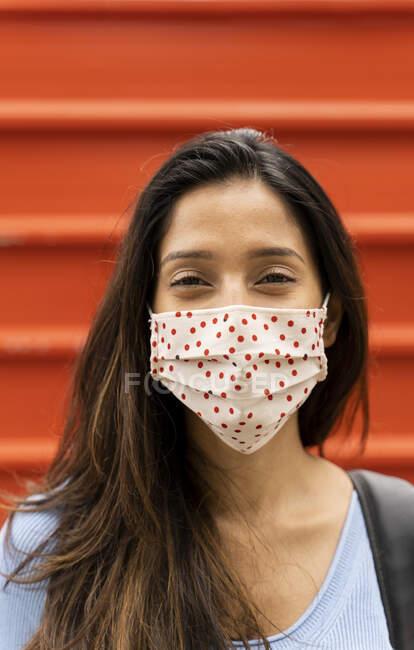 Посмішка жінка з захисною маскою обличчя стоїть проти затвора під час COVID-19 — стокове фото