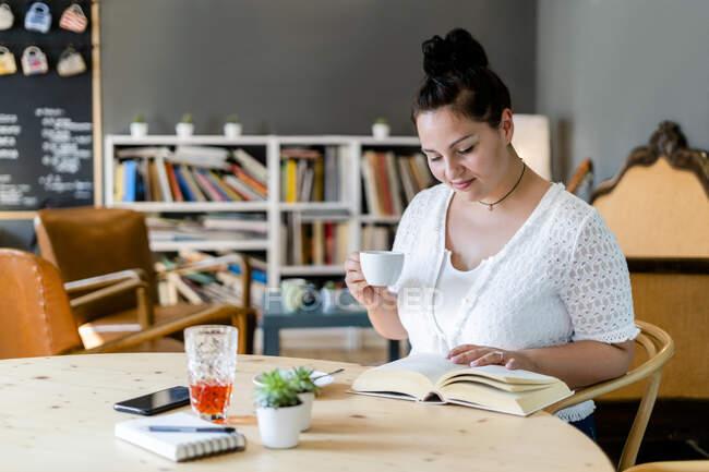 Voluptuosa mulher segurando xícara de café enquanto lia livro na mesa no restaurante — Fotografia de Stock