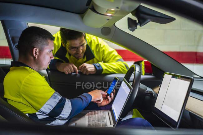Programador masculino mostrando telefone celular para colega enquanto sentado em carro elétrico — Fotografia de Stock