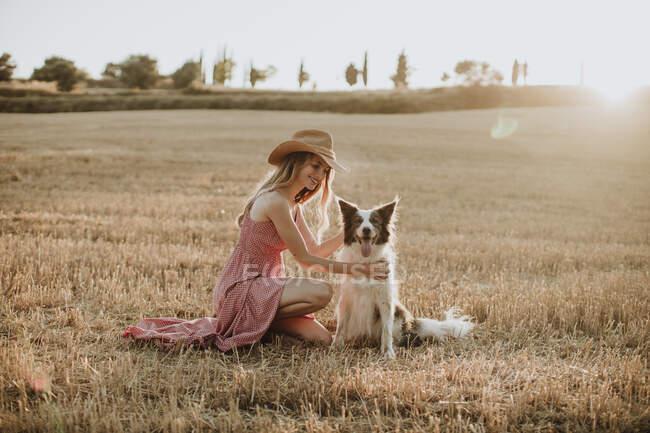 Mujer disfrutando con perro collie frontera en campo de trigo durante la puesta del sol - foto de stock