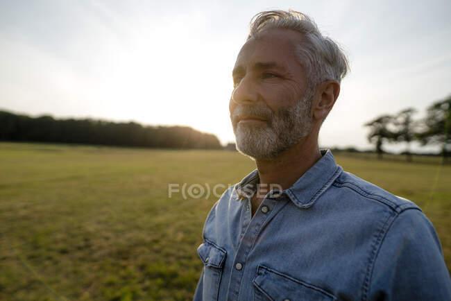 Conteúdo homem maduro em um prado no campo — Fotografia de Stock