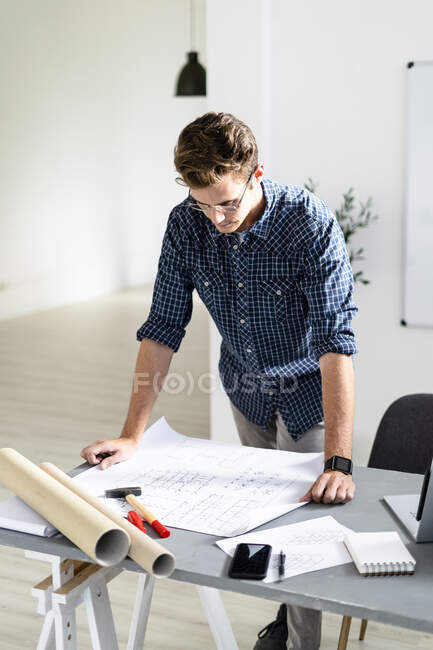 Architect analyzing blueprint while standing by desk at office — Stock Photo