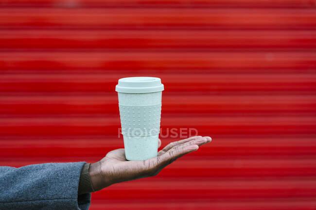 Hombre sosteniendo taza de café desechable contra la pared roja - foto de stock