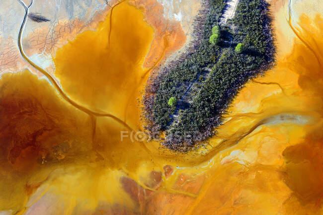 Vista aérea de un pequeño parche verde de terreno rodeado de ácidos marrones de la zona de las minas de Rio Tinto - foto de stock