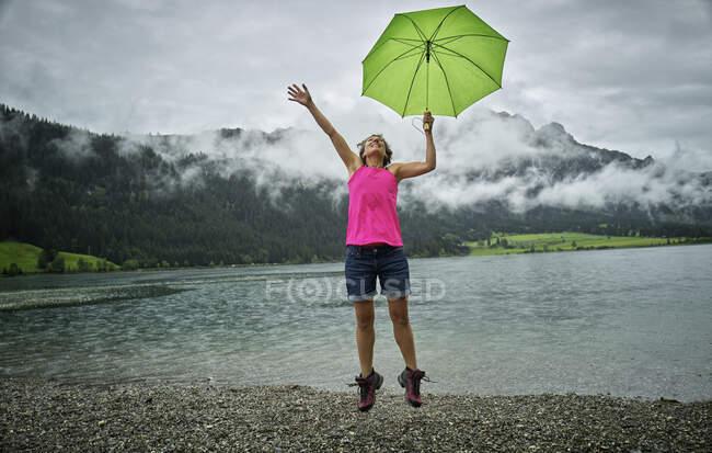 Mulher madura feliz segurando guarda-chuva enquanto saltando em Haldensee lakeshore durante a estação chuvosa — Fotografia de Stock