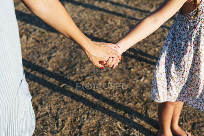 Мать держит дочь за руки, стоя на земле — стоковое фото