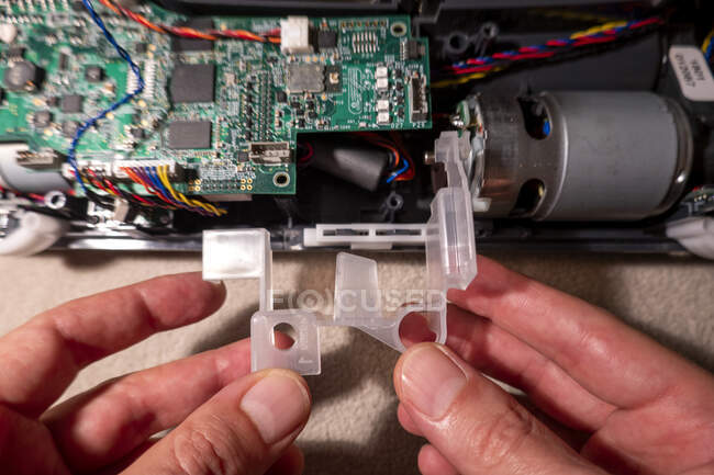 Руки зрілої людини ремонтують роботизований пилосос. — стокове фото